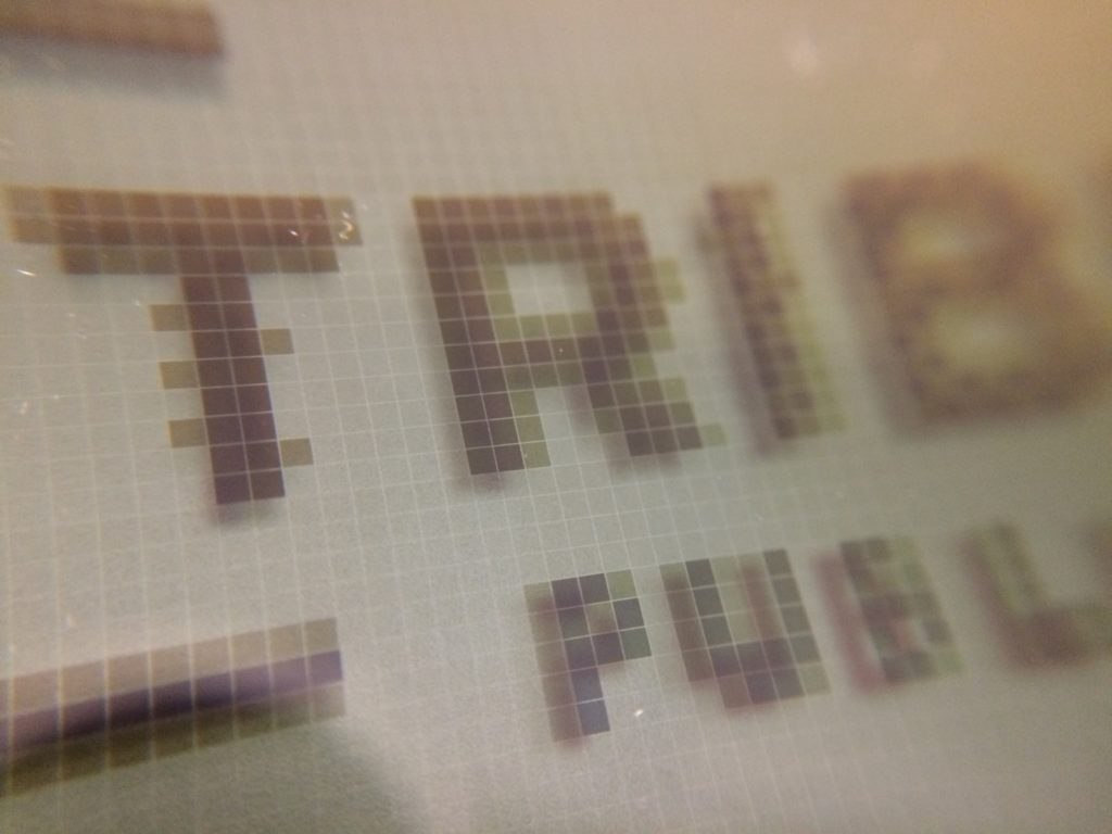 Closeup of Tribune Publishing logo in 8-bit grayscale